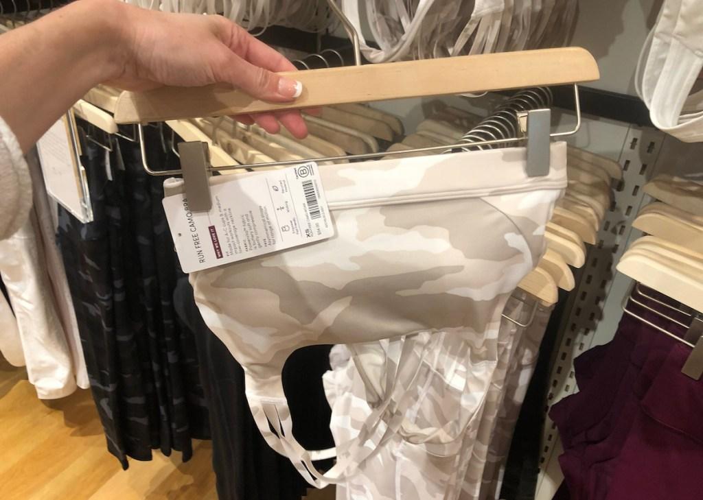 hand holding camo bra on hanger