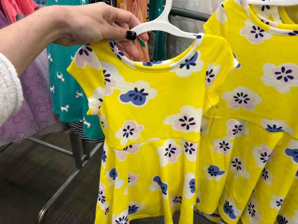 yellow dress on hanger held by hand in store