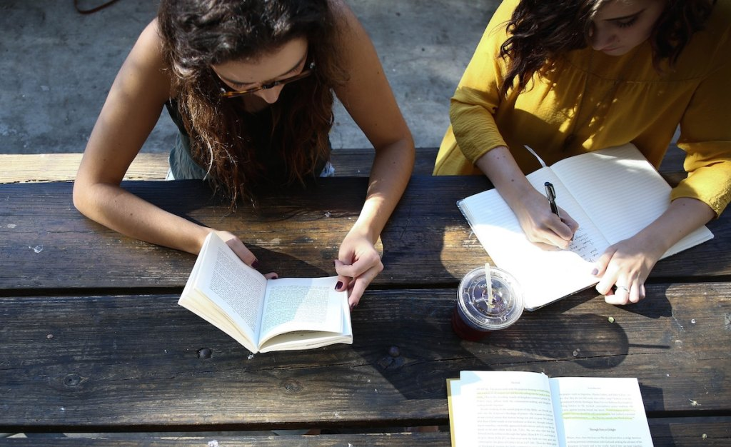 women reading and writing at picnic table