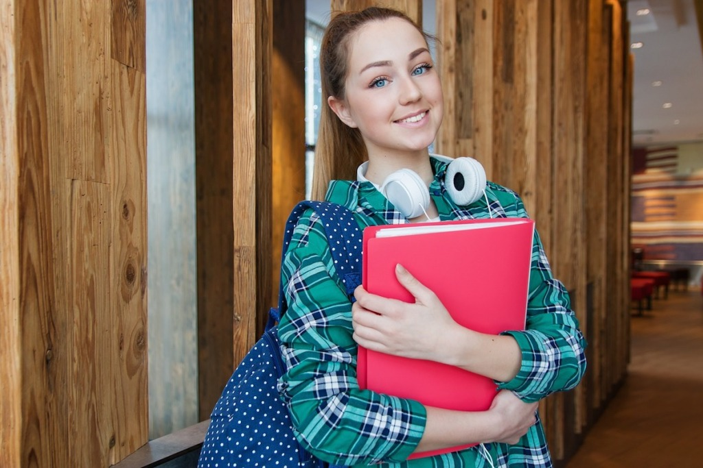 student holding red folder with headphones on neck