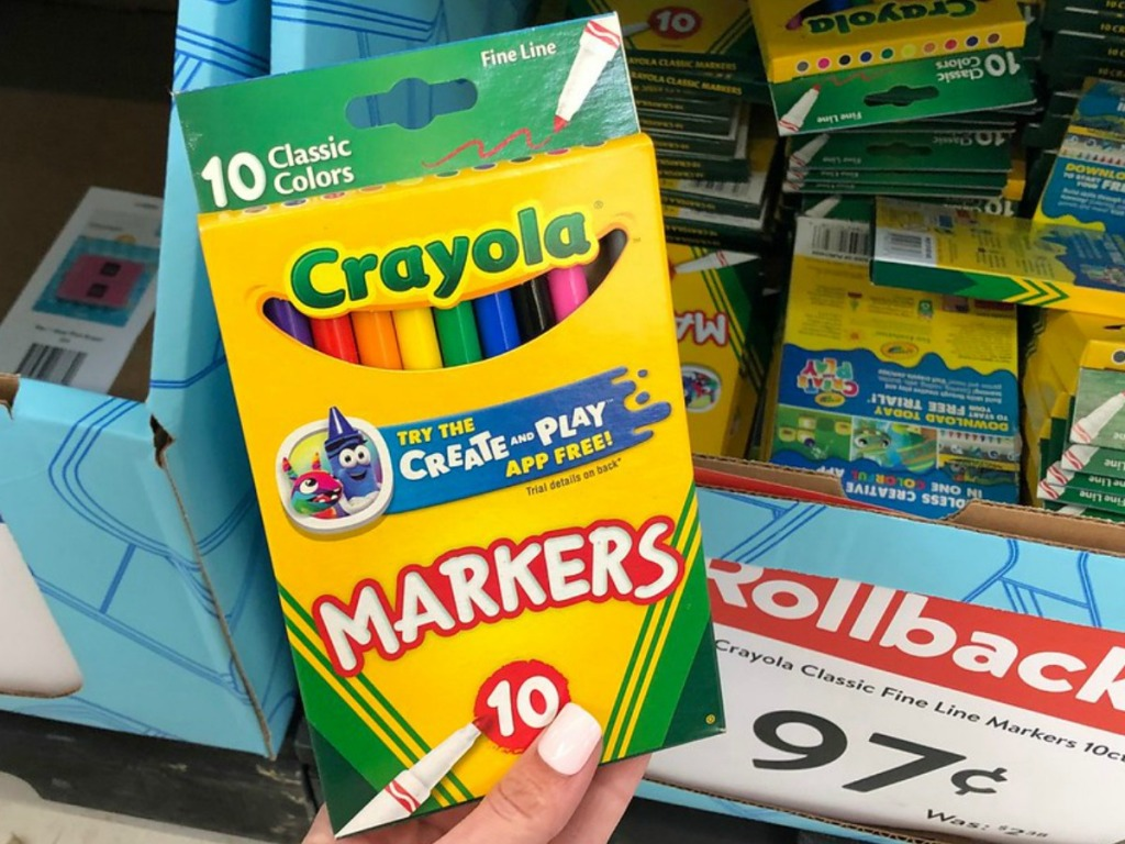 hand holding package of markers by store sign