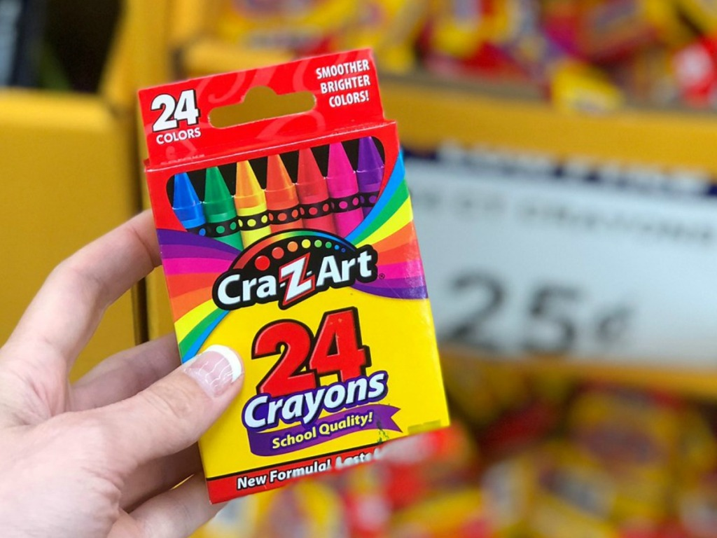 hand holding box of crayons by store display