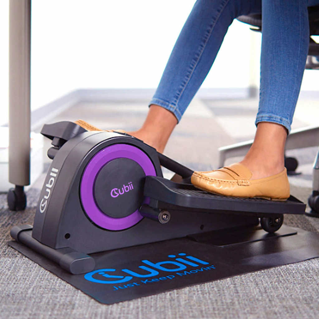 woman with flats on using cubii under desk elliptical