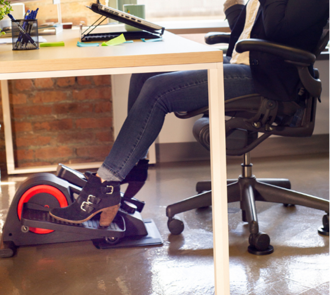 woman using cubii under desk ellpitcal with boots