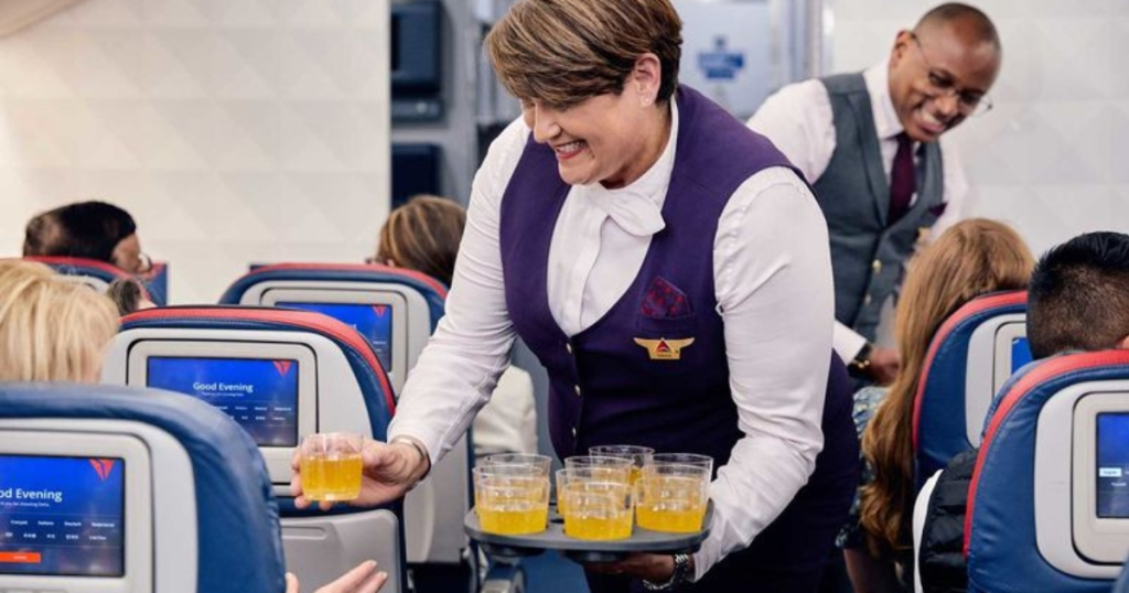Delta flight attendant handing out cocktails