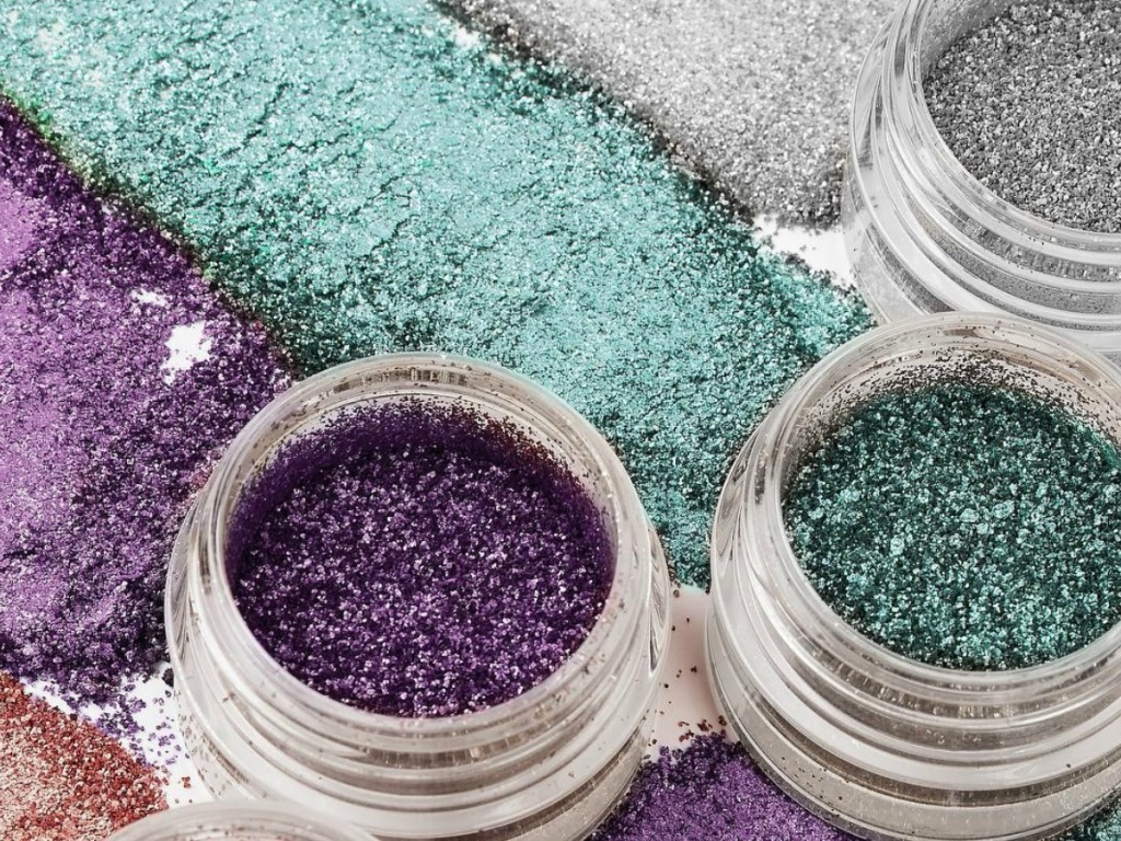 open containers of glitter make up spread on counter
