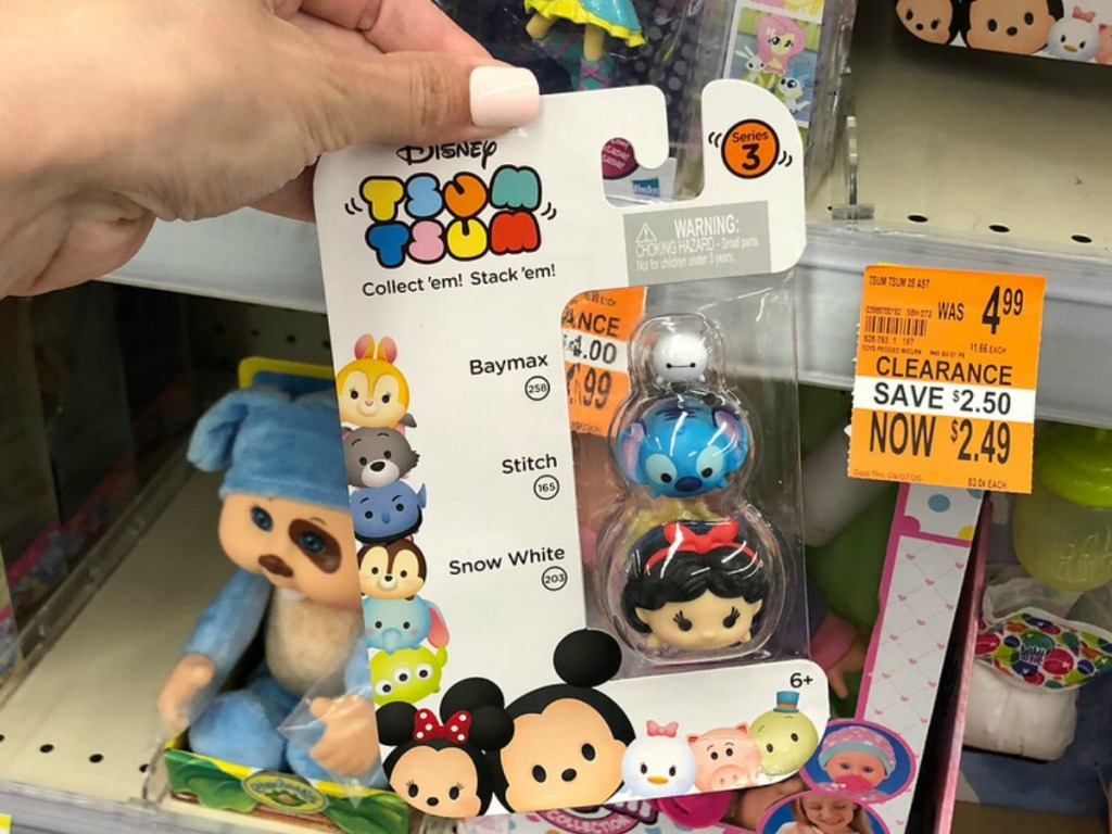 small Disney toys in package held by hand in store