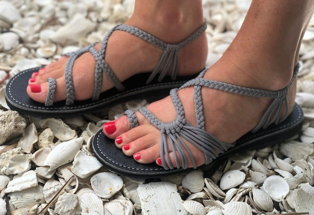 feet wearing grey braided sandals with pink toenail polish