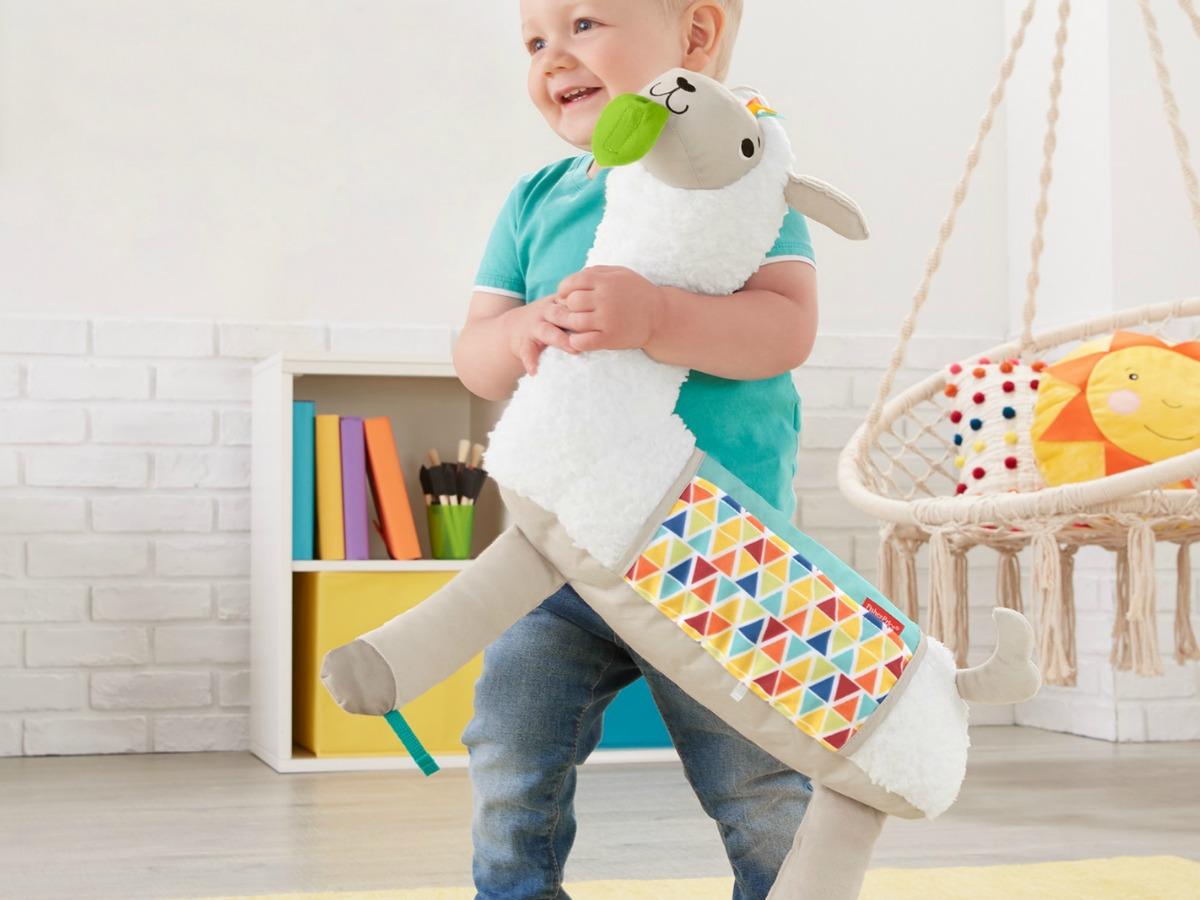 toddler boy walking around room holding plush toy