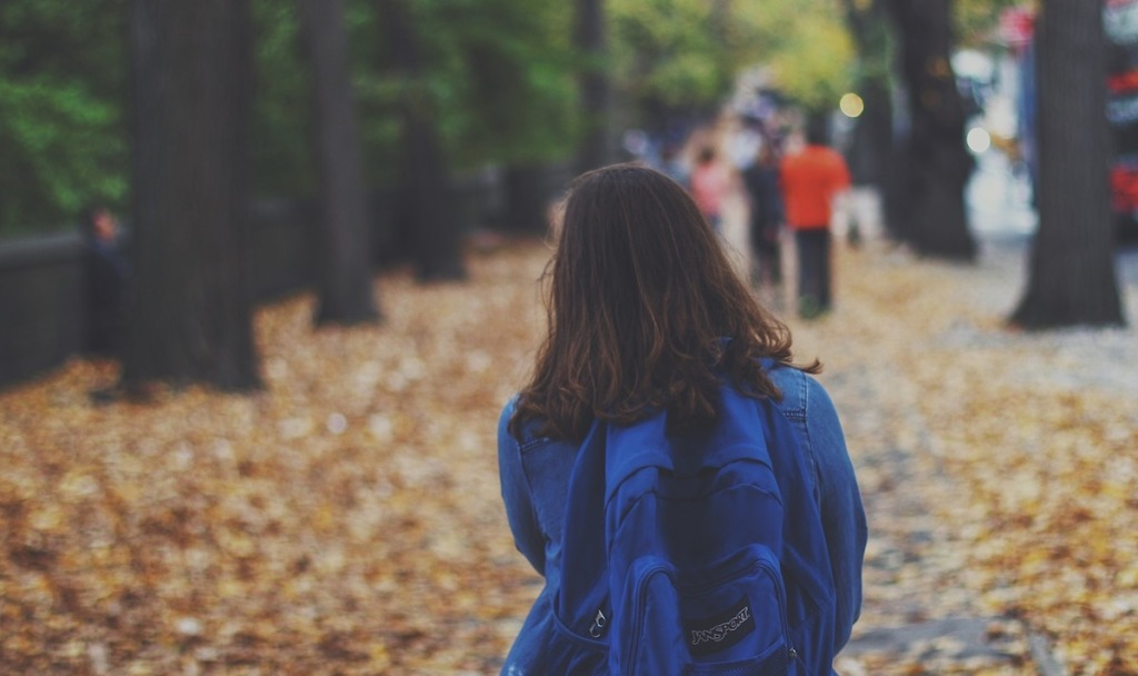 girl with blue backpack walking down leave covered street