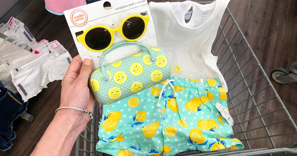 holding up lemon sunglasses in front of lemon themed outfit at walmart