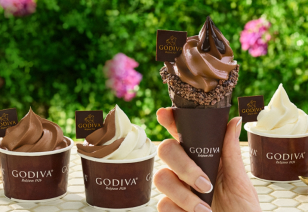 hand holding a chocolate soft serve ice cream cone with cups of soft serve in background