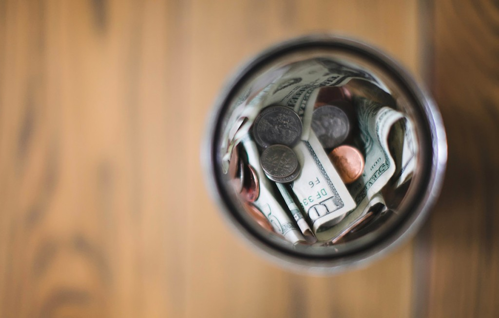 money bills and coins in glass jar