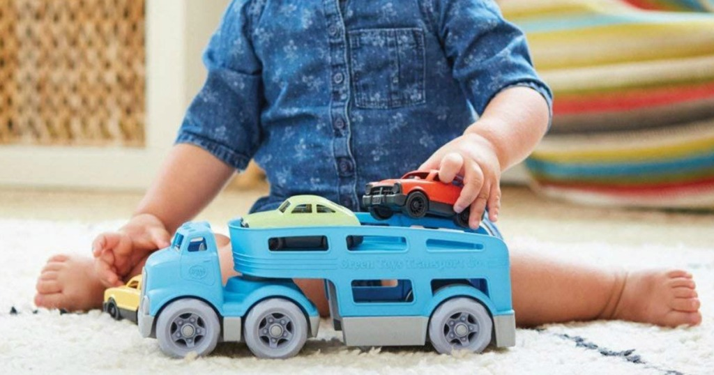 kid playing with blue truck and cars