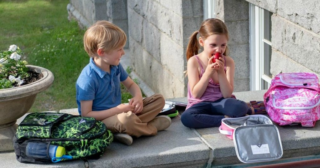 boy and girl sitting on ledge at school with backpacks girl is eating apple