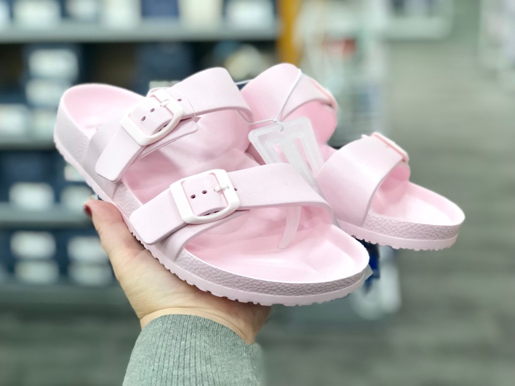 hand holding pink shoes in store