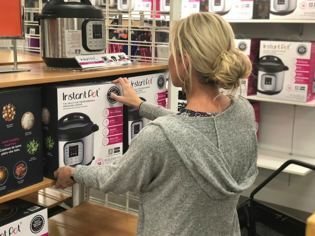 woman in store taking pressure cooker off shelf
