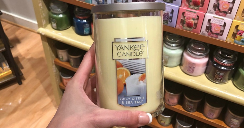 hand holding yellow candle by store display