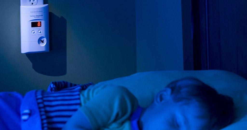 kid sleeping with kidde carbon monoxide alarm with digital display plugged in