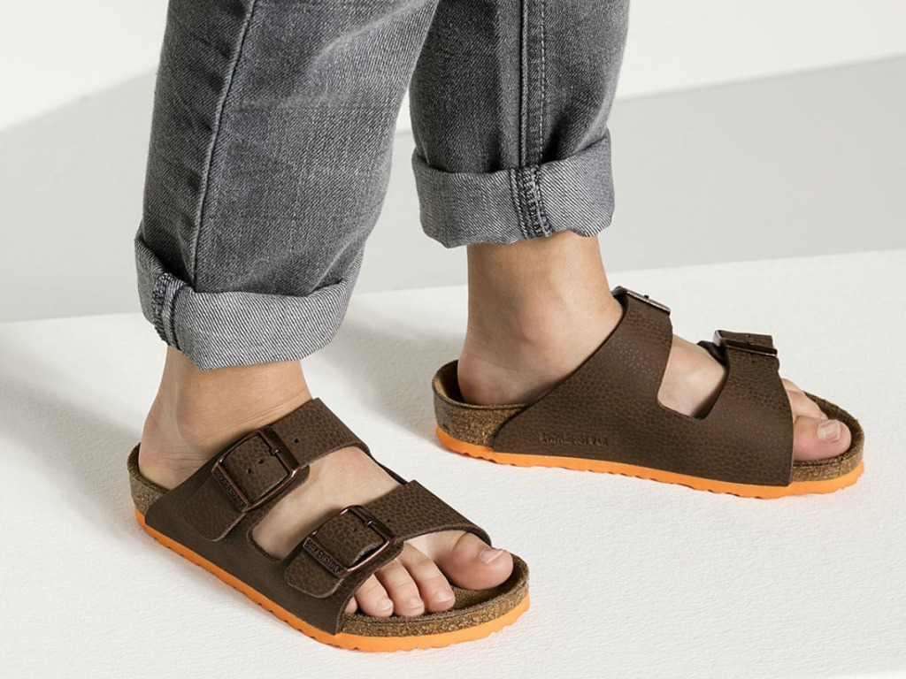 kid in jeans wearing 2 strap brown sandals