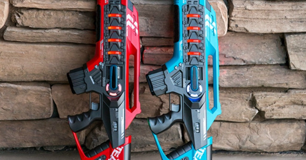 two laser tag blasters propped against a wall