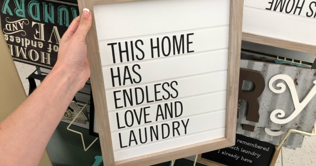 hand holding a white laundry sign in store