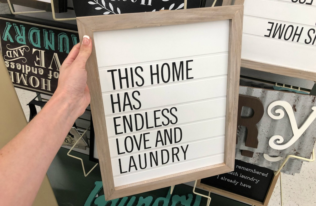 white wooden this home has endless love and laundry sign being held in store