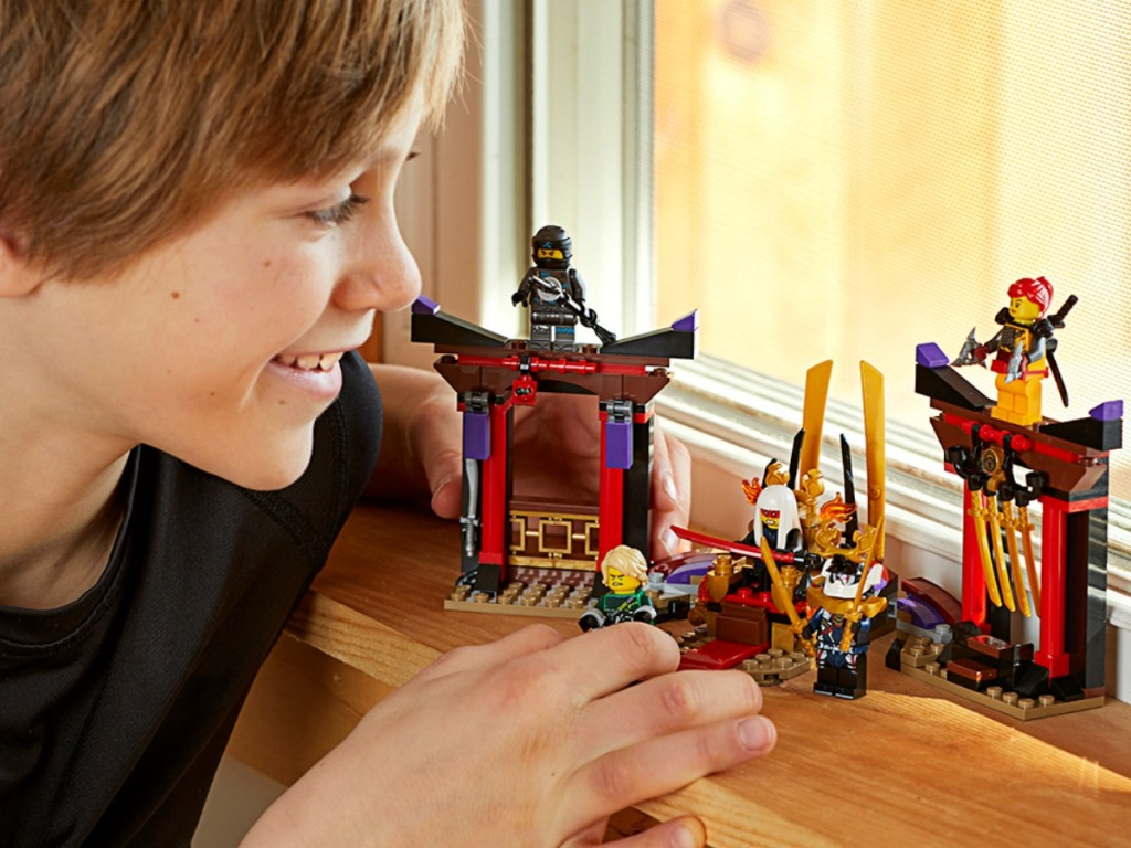boy playing with legos on window