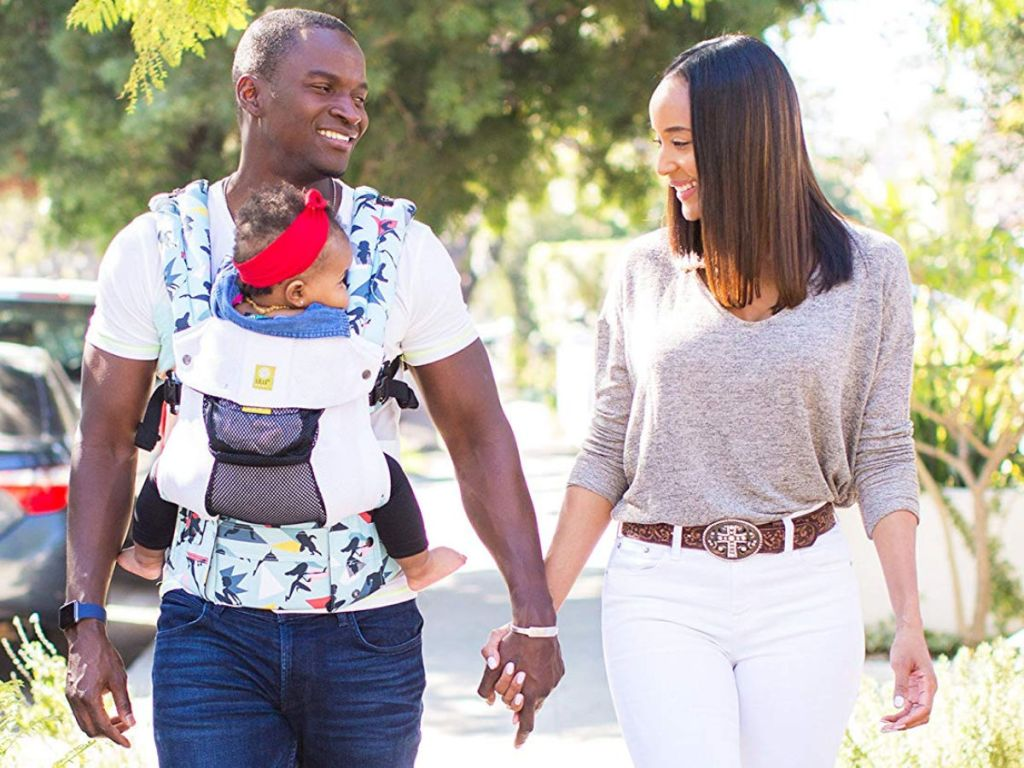 mom and dad walking with dad holding baby in lillebaby incredibles 2 disney carrier