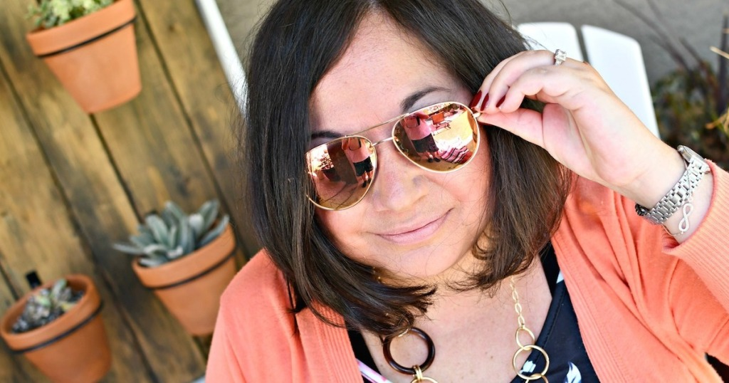 woman wearing orange mirrored sunglasses and orange top outside