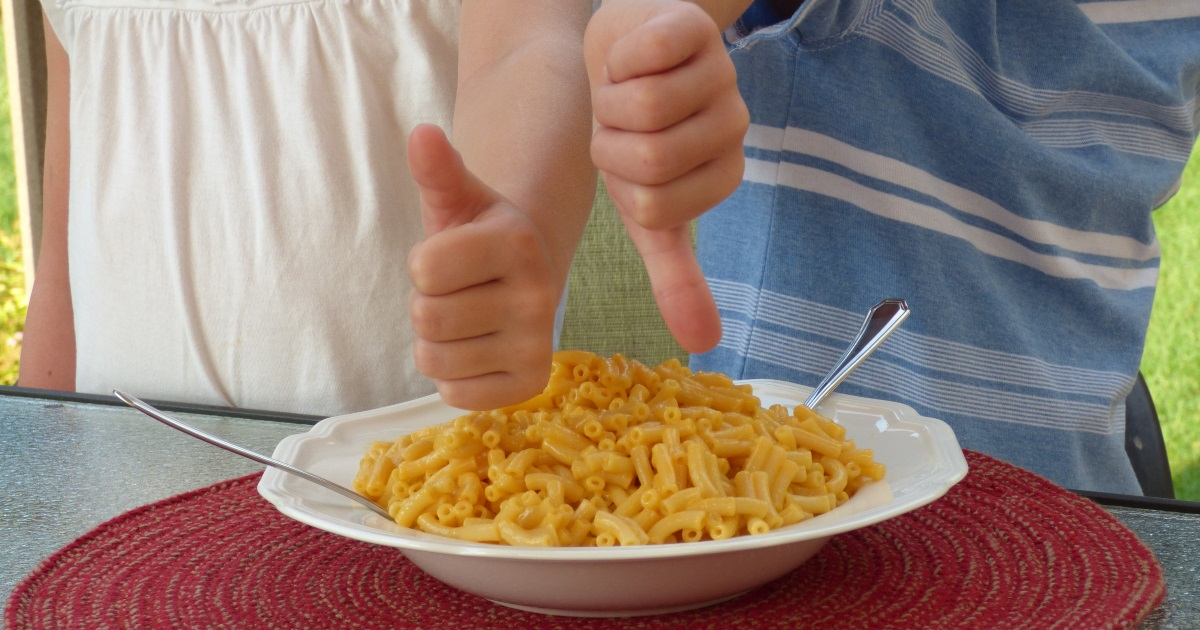 girl gibing the thumbs up and boy giving the thumbs down over mac and cheese