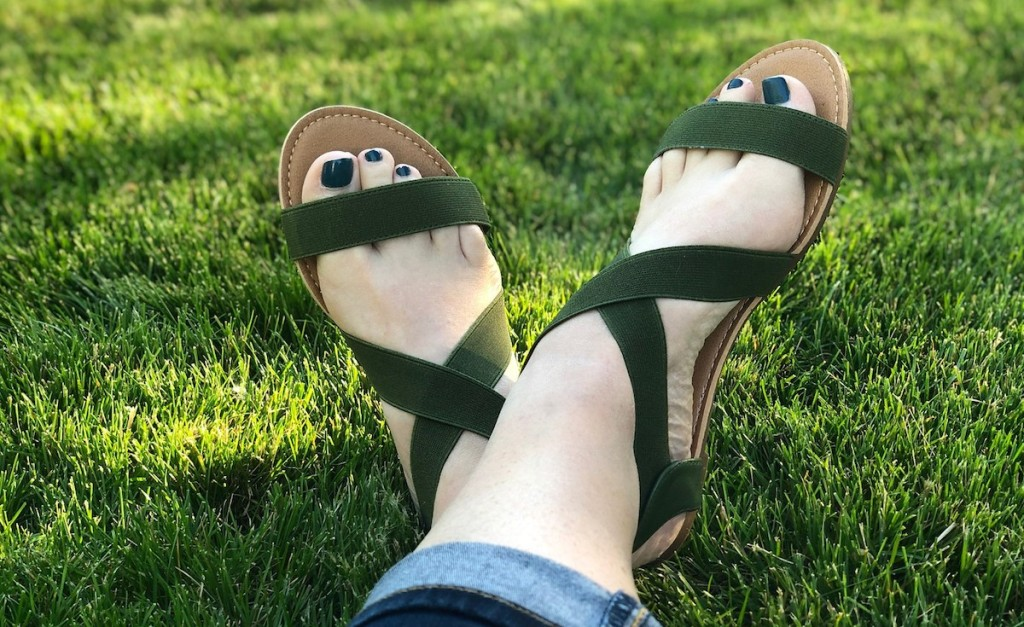 feet wearing dark green sandals in grass