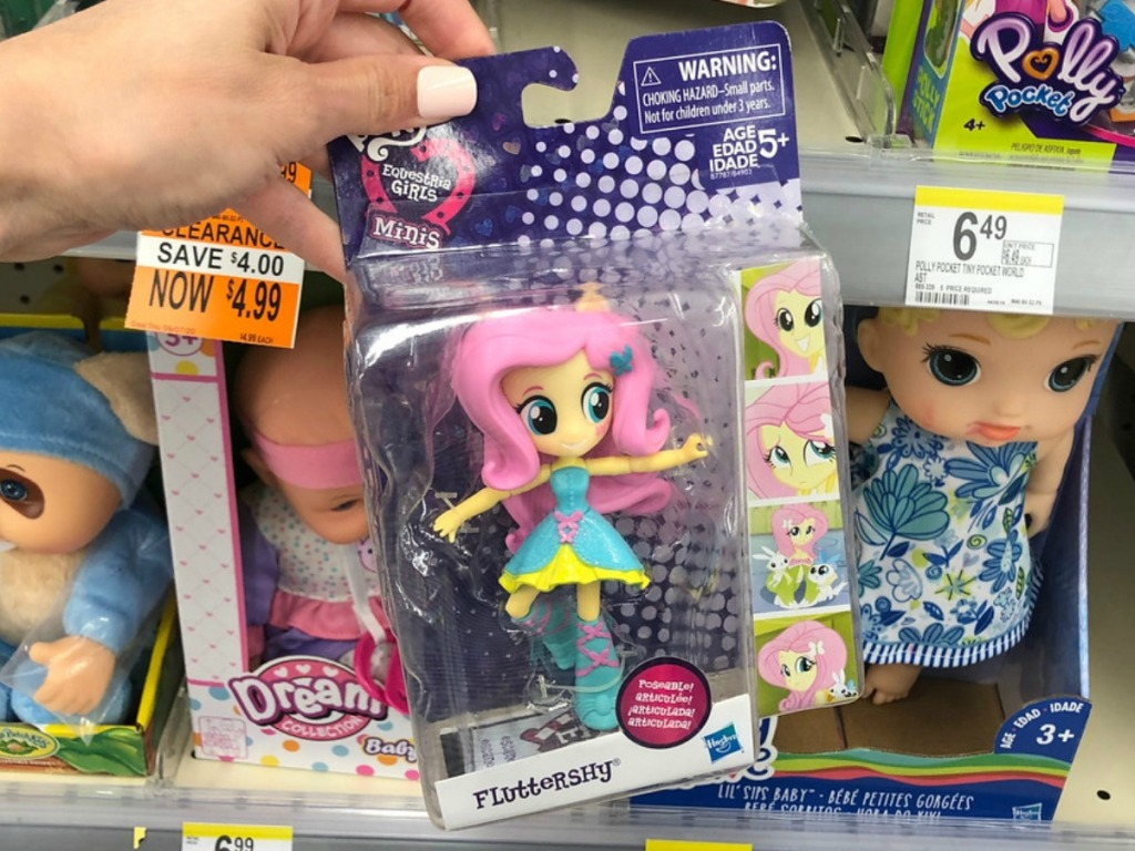 hand holding toy in package with pink doll at store