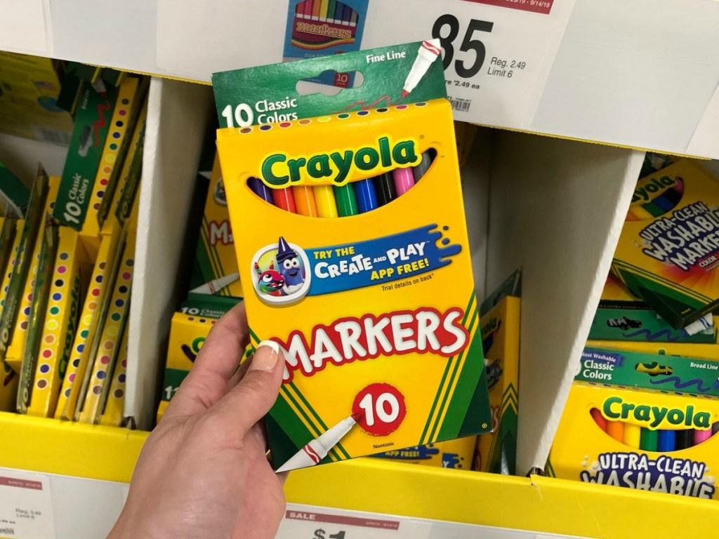 Crayola Markers held up in front of school supply bin