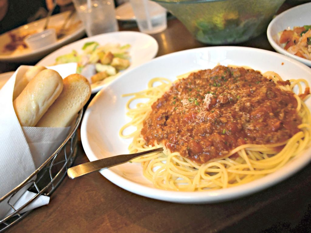 olive garden meat sauce pasta at table with bread and salad