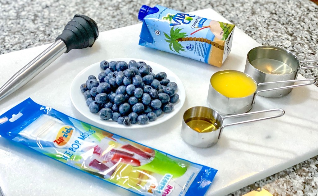 fresh blueberries and measuring cups with various liquids inside