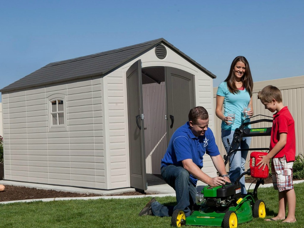 family starting lawn mower outside by shed