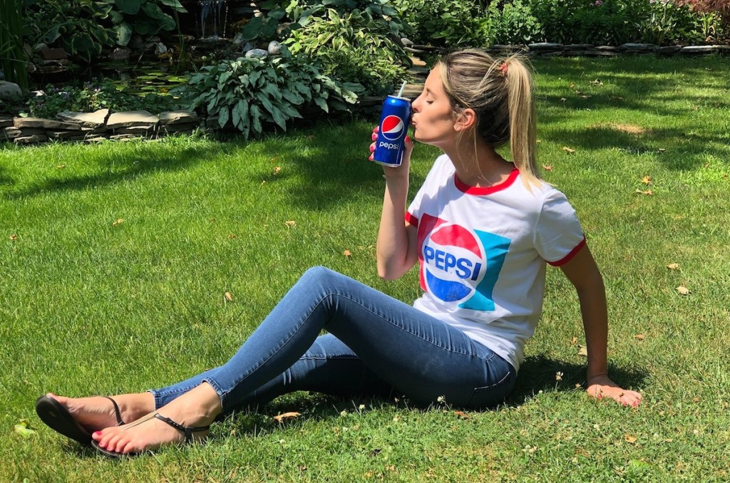 woman wearing pepsi shirt with soda in grass