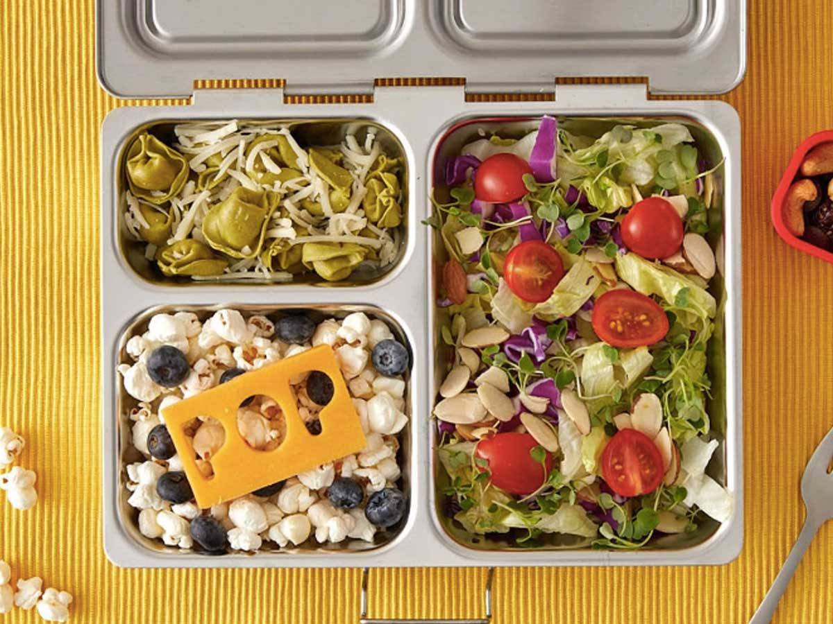 metal lunchbox with pasta, salad, fruit and popcorn filling three compartments