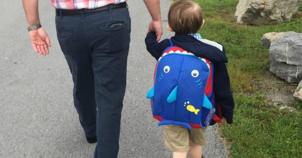 child with cute backpack holding dads hand