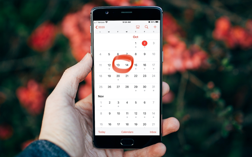 hand holding phone with calendar amazon prime dates circled
