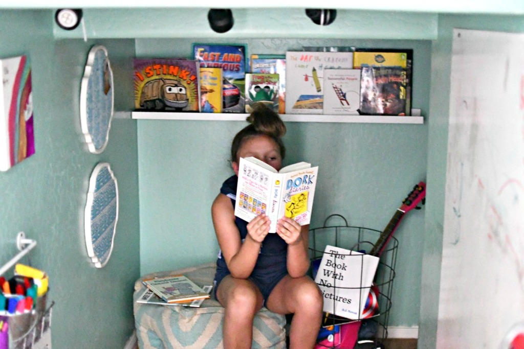 girl reading book in book nook