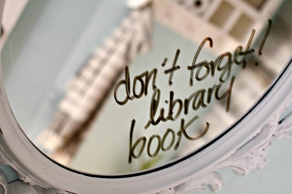 library book reminder written on bathroom mirror