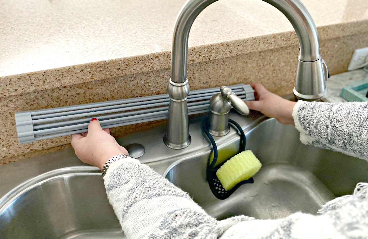rolling up a drying mat behind the faucet