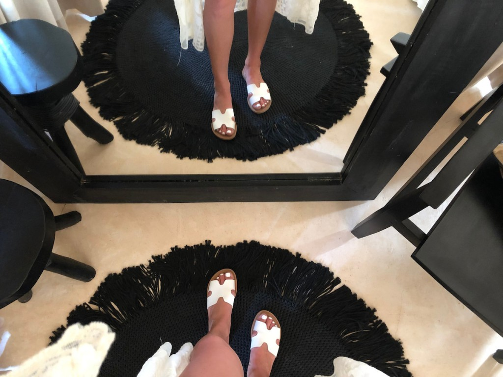 mirrored image on feet wearing white sandals and round fringe black rug