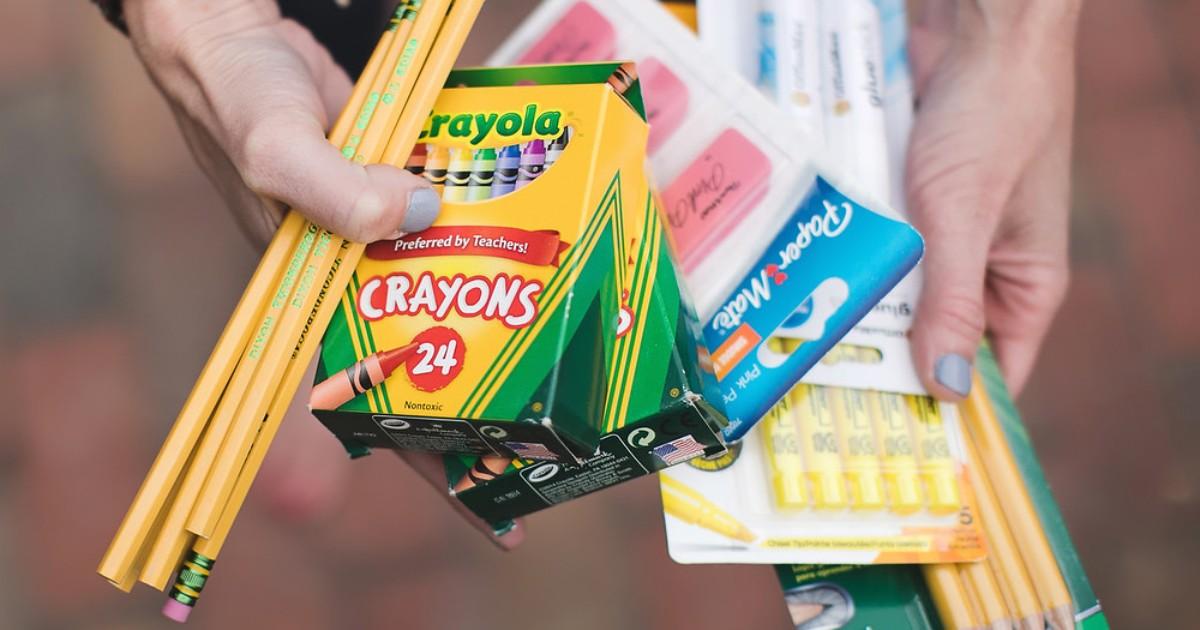 hands holding school supplies