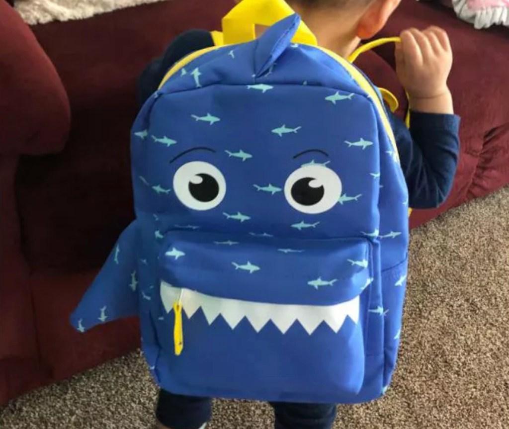 toddler wearing blue shark backpack