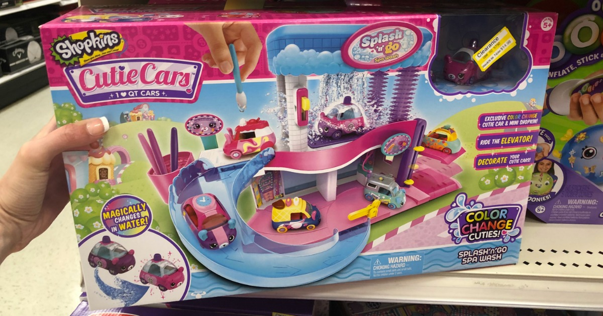 hand holding a shopkins cutie car set in front of a Target store shelf