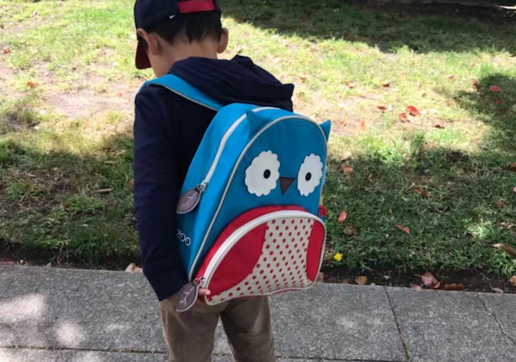 boy wearing blue and red owl backpack
