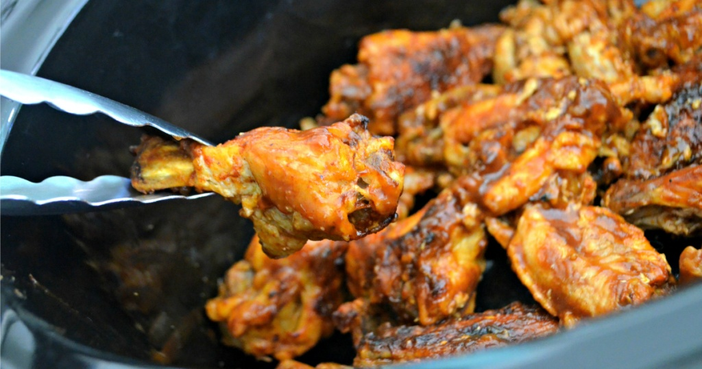 pulling out chicken wing from slow cooker